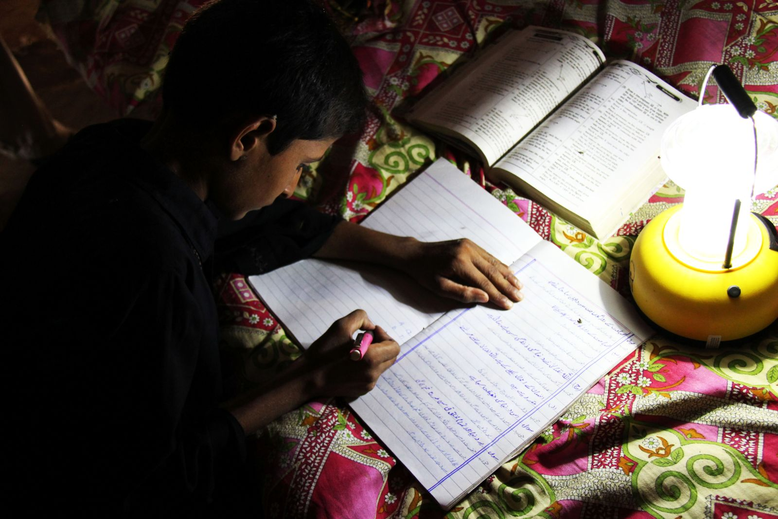 Pakistan child does his homework via a solar lamp