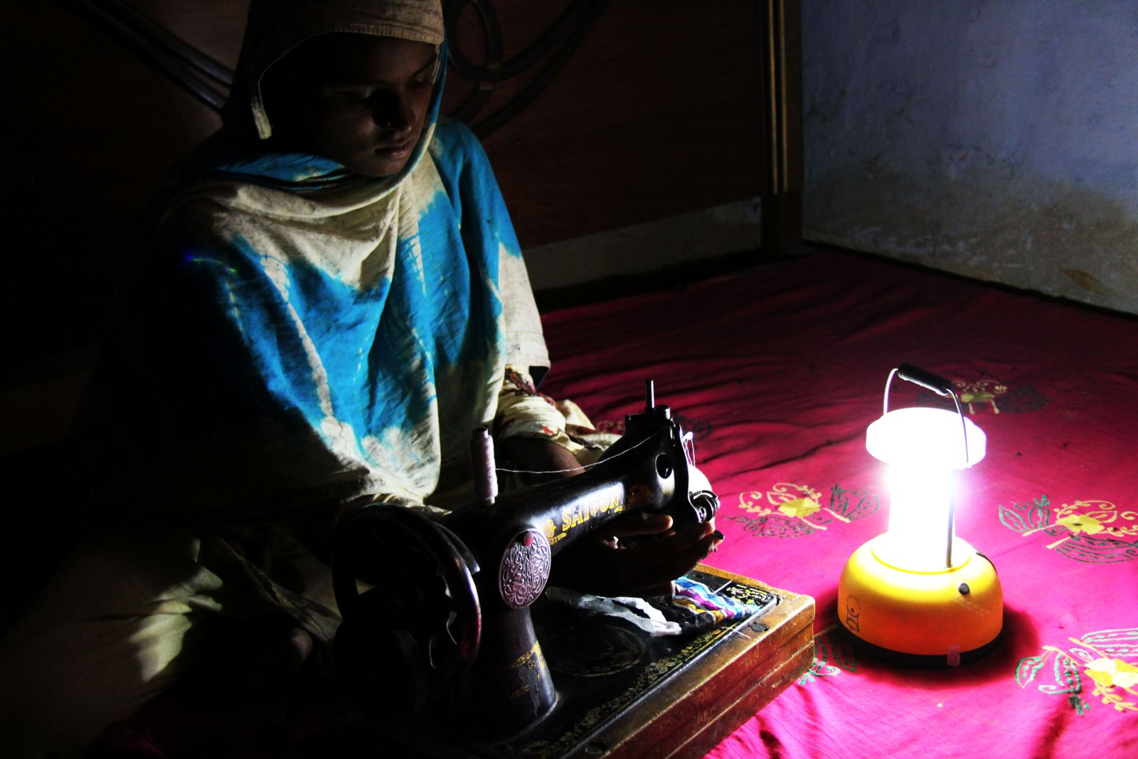 A woman works under the light of a solar lamp