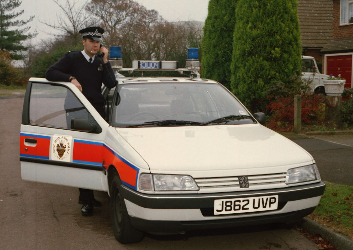 Police officer posing with car in the 1990s